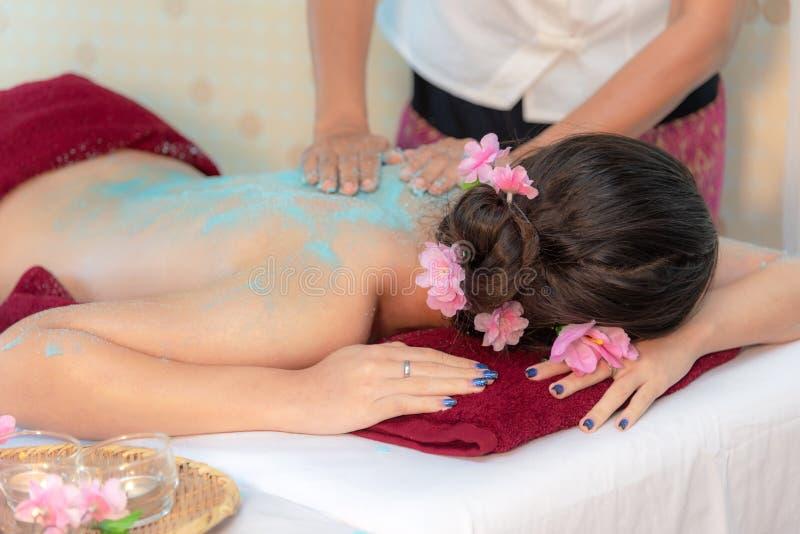 做与治疗盐和糖的男按摩师按摩温泉在泰国温泉生活方式的亚裔妇女身体,因此放松和豪华 免版税库存照片