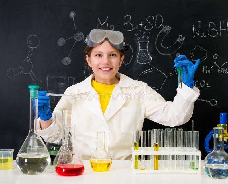 做与液体的白色褂子的女小学生实验 库存照片