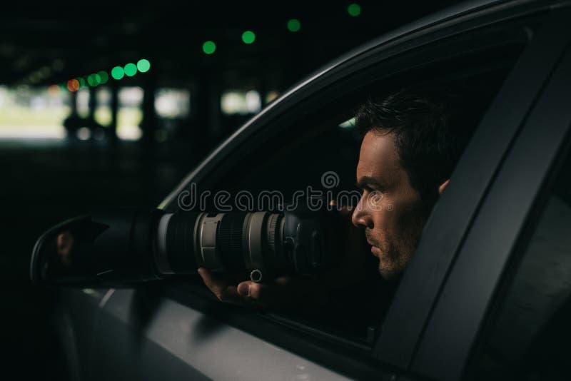 做与照相机的男性无固定职业的摄影师侧视图监视从他的 免版税图库摄影