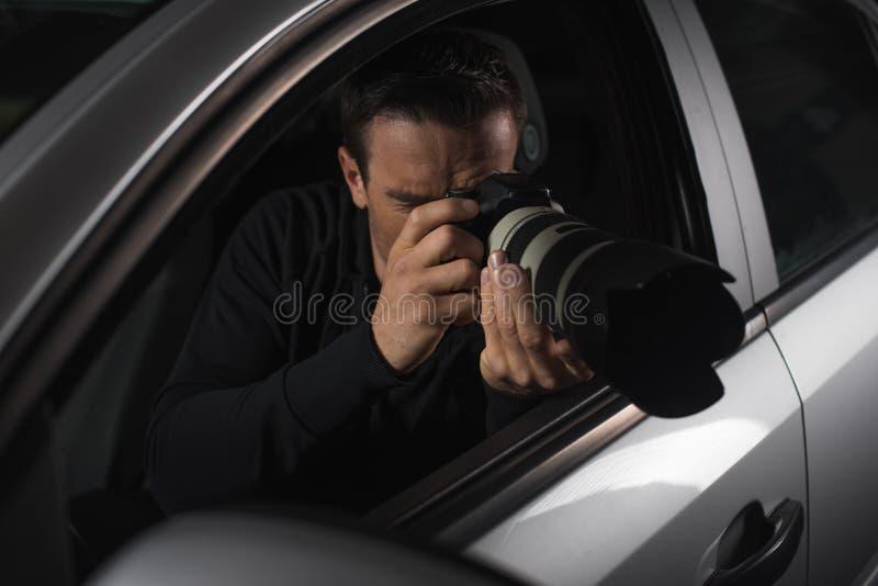 做与照相机的男性无固定职业的摄影师监视从他的 图库摄影