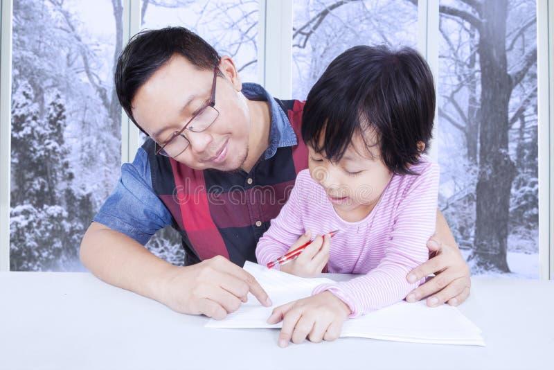 做与爸爸的逗人喜爱的小女孩家庭作业 免版税库存图片