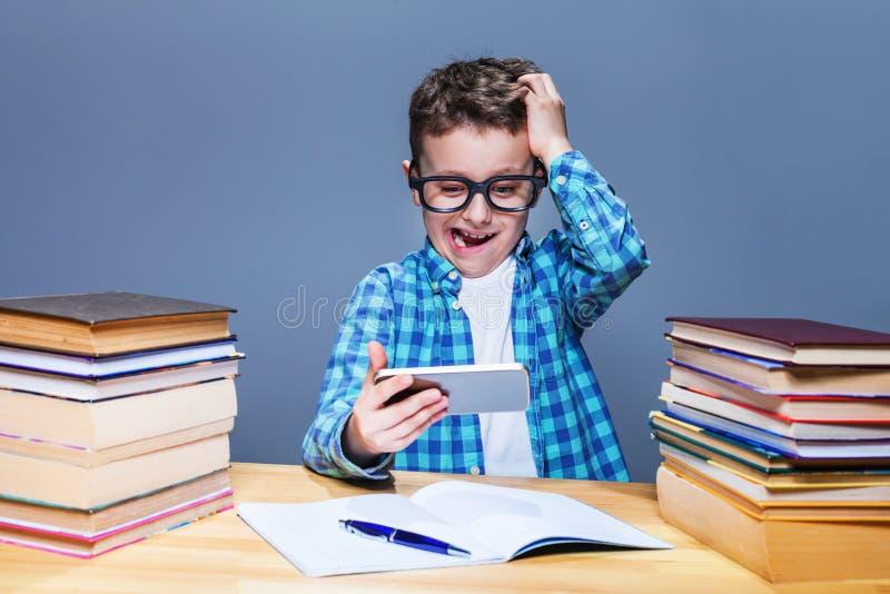 做与片剂个人计算机的聪明的男小学生家庭作业 图库摄影