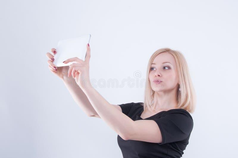 做与片剂的妇女selfie在白色隔绝了背景 关闭看在wh的黑礼服的年轻白肤金发的美丽的女孩 免版税图库摄影