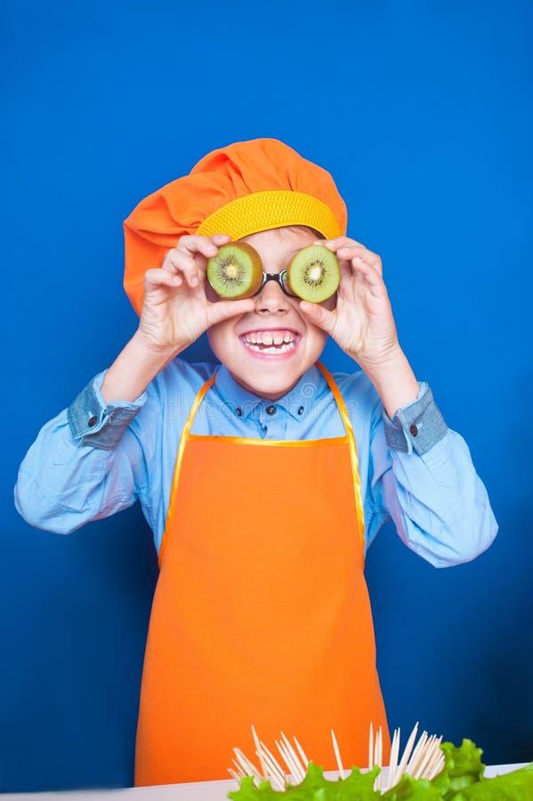 做与猕猴桃切片的滑稽的在厨房里帮忙的仆人鬼脸在眼睛 库存图片