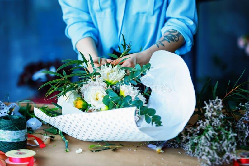 做与玉树poplaraceous杨属和菊花单一带头的Anasta的迷人的快乐的女性售货员花束 免版税库存照片