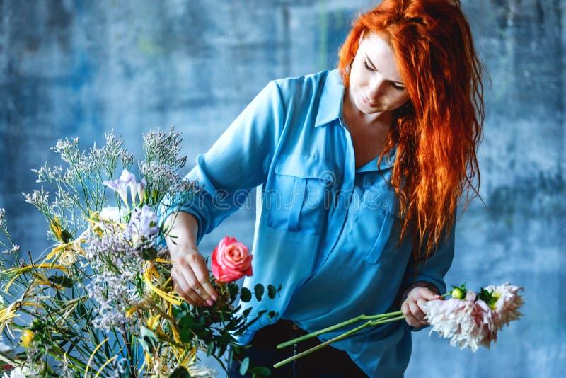 做与玉树poplaraceous杨属和菊花的迷人的快乐的女性售货员透明尸体花束 免版税库存照片