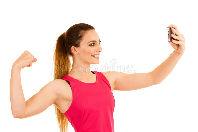做与胳膊的美好的运动的妇女身分selfie在白色背景的拳头 库存照片