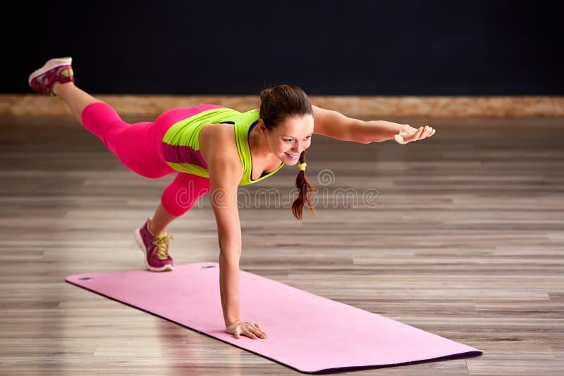 做与腿的亭亭玉立的健身少妇运动员女孩锻炼在桃红色瑜伽席子 库存照片