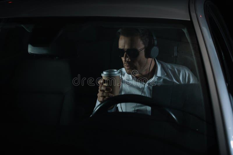 做与膝上型计算机的监视和喝咖啡的耳机的男性私家侦探 图库摄影