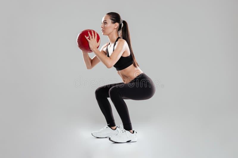 做与药丸的可爱的少妇运动员蹲坐 库存照片