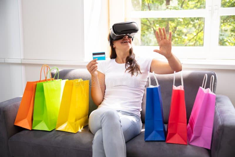 做与虚拟现实玻璃的妇女购物 免版税库存照片