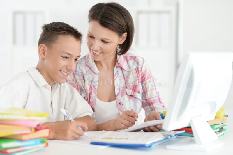 做与计算机的十几岁的男孩画象家庭作业 免版税库存照片