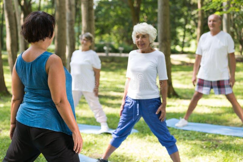 做与辅导员的前辈瑜伽 免版税库存照片