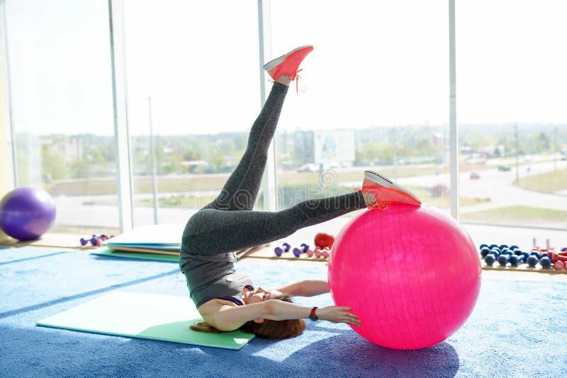 做与适合的球的运动的妇女新闻锻炼在健身房 概念:生活方式、健身、有氧运动和健康 免版税库存照片