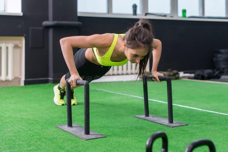 做与酒吧的年轻人适合的妇女水平的俯卧撑在健身房 免版税图库摄影