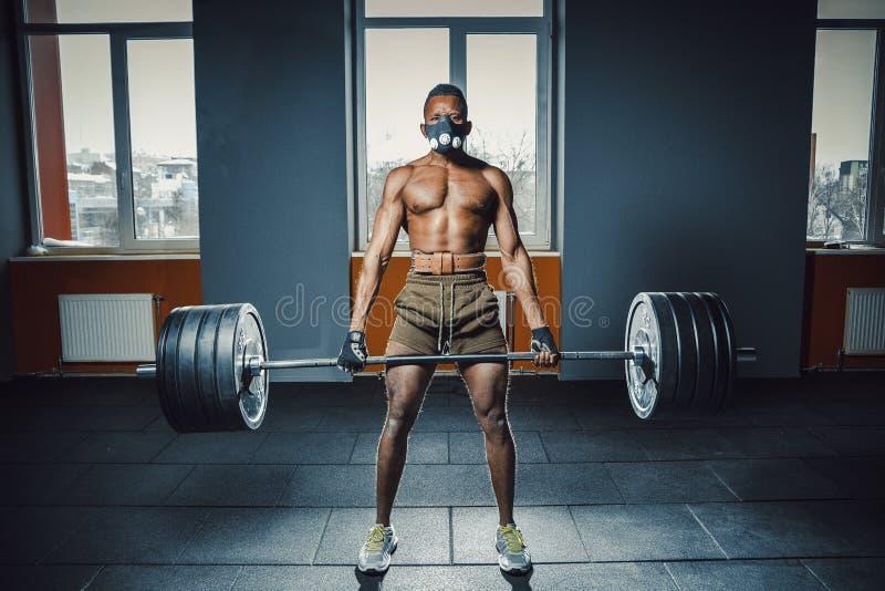 做与重的杠铃的体育面具的非裔美国人的运动人deadlift 在窗口对面的黑人举的杠铃 emotiona 库存照片