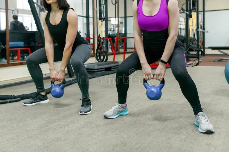 做与重量的两名年轻健康妇女锻炼在健身房 健身,体育,训练,人们,健康生活方式概念 库存图片