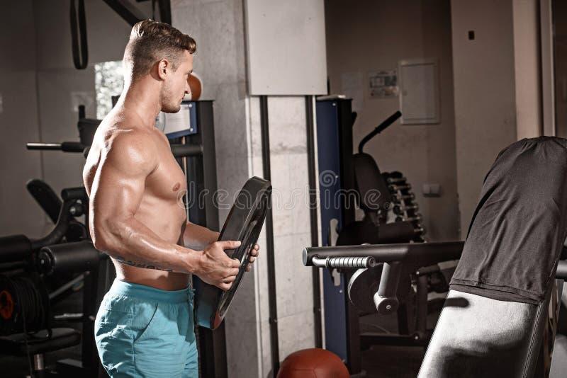 做与重量的肌肉爱好健美者人锻炼在健身房 免版税库存照片