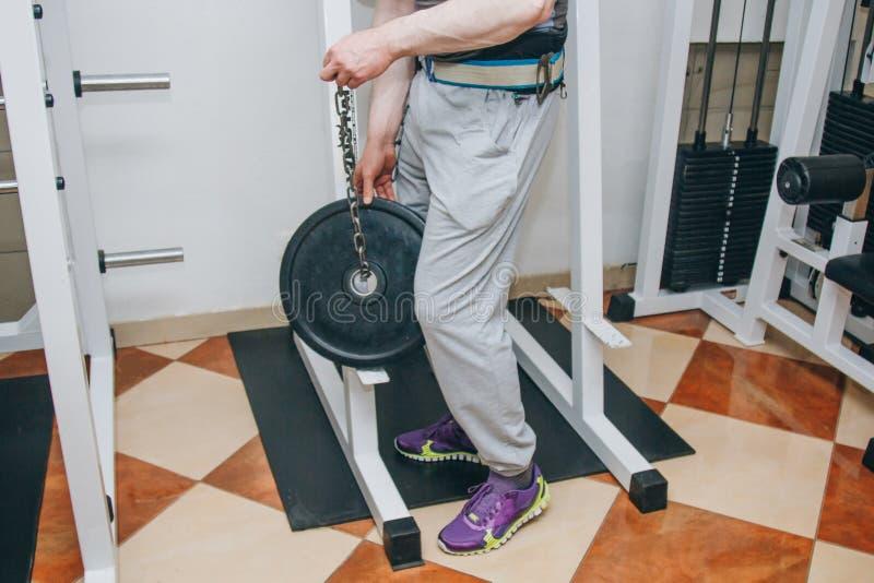 做与重量的运动员锻炼在腰带在训练的中心 r 免版税库存照片