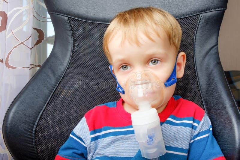 做与雾化器的男孩吸入 免版税库存图片
