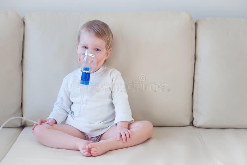 做与面具的女婴吸入在她的面孔 图库摄影