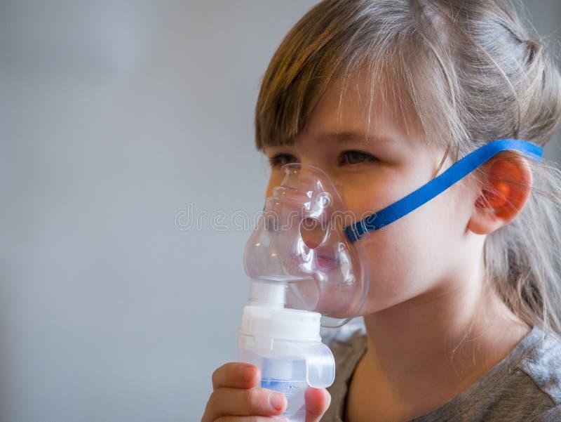 做与面具的孩子吸入在他的面孔 哮喘问题概念 免版税库存照片