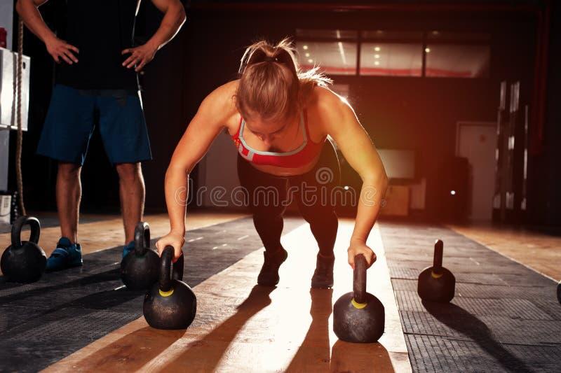 做与水壶响铃的肌肉女孩俯卧撑 免版税库存照片