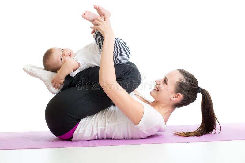 做与婴孩的母亲瑜伽锻炼 免版税库存图片