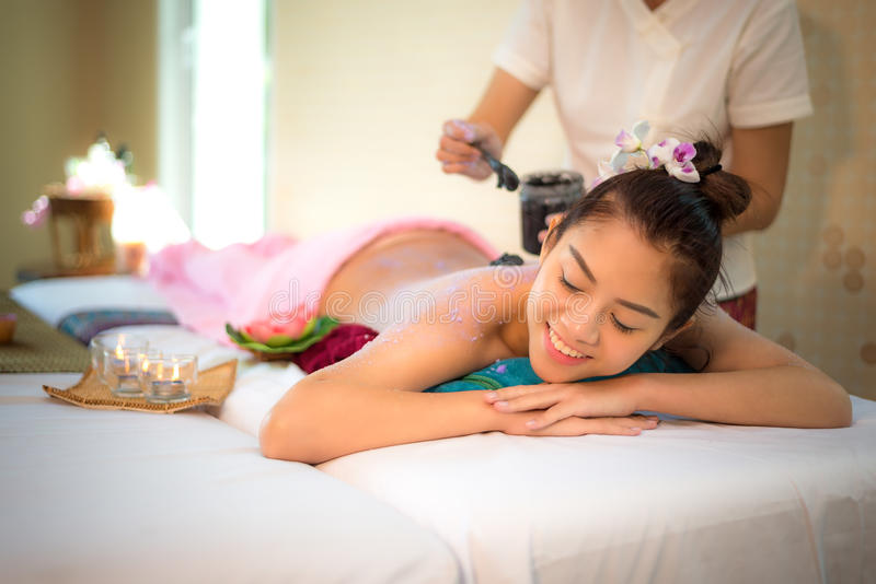做与治疗泥的男按摩师按摩温泉在泰国温泉生活方式的亚裔妇女身体,因此放松和豪华 免版税图库摄影