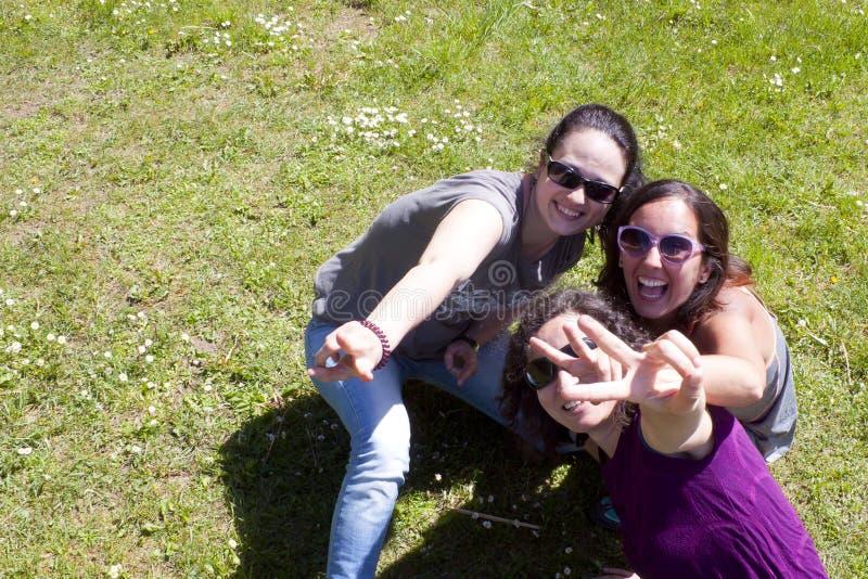 做与他们的手指的三个女孩V形标志 免版税库存照片