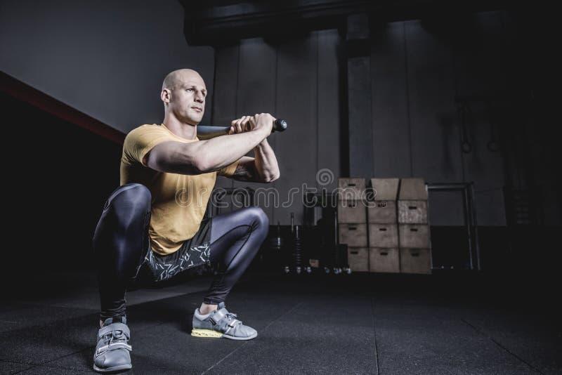 做与Clubbel的运动员锻炼在健身房 免版税库存照片