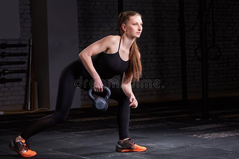 做与kettlebell的年轻健身妇女crossfit锻炼在黑暗的背景 免版税库存照片