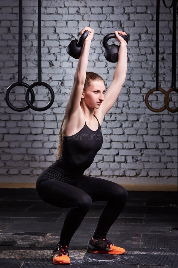 做与kettlebell的年轻健身妇女crossfit锻炼对砖墙 免版税库存照片