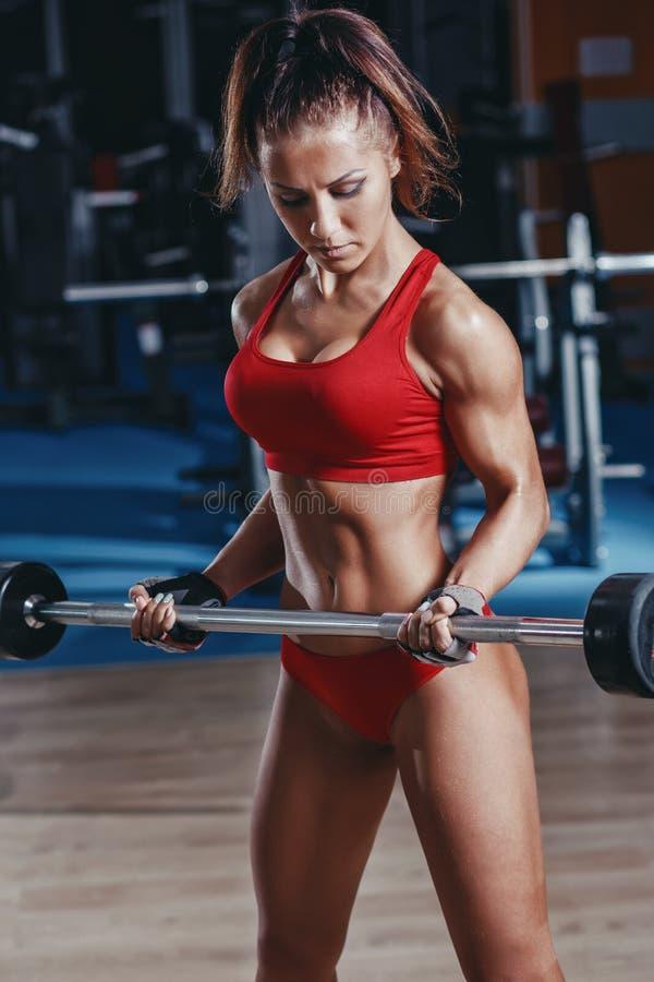做二头肌杠铃卷毛的性感的年轻竞技女孩在健身房行使 免版税库存照片