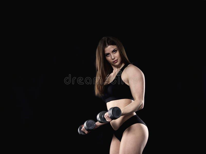 做二头肌的女孩在健身房行使 免版税图库摄影