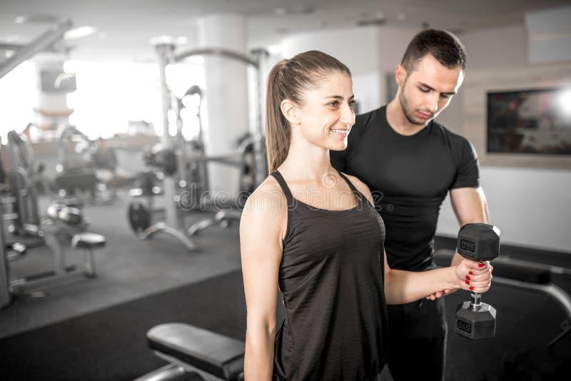 做二头肌的妇女在与她的个人教练员的健身房卷曲 库存照片