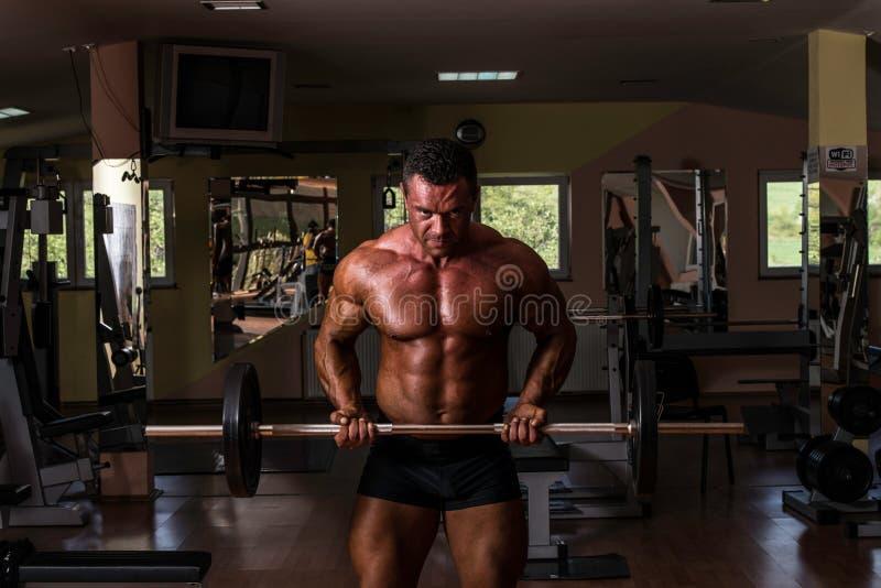 做二头肌的爱好健美者重量级的锻炼与杠铃 免版税库存图片