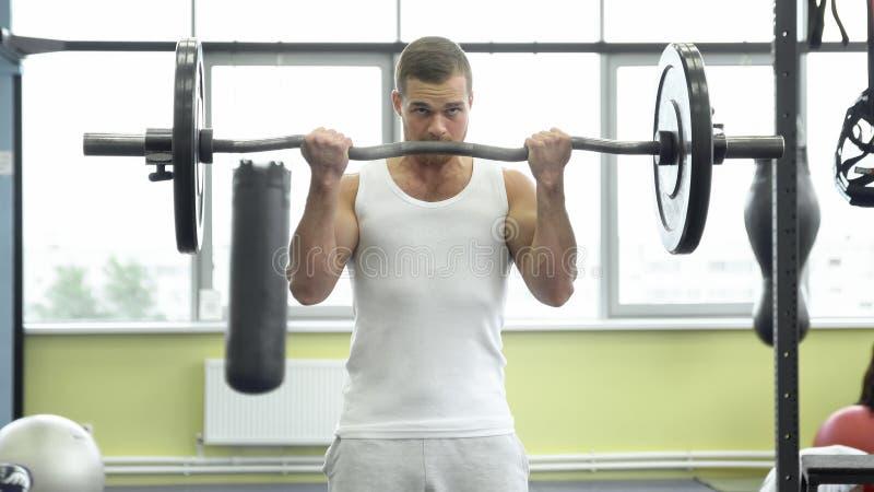 做二头肌的运动员锻炼与杠铃 在健身房的年轻肌肉人火车 CrossFit训练 免版税库存图片