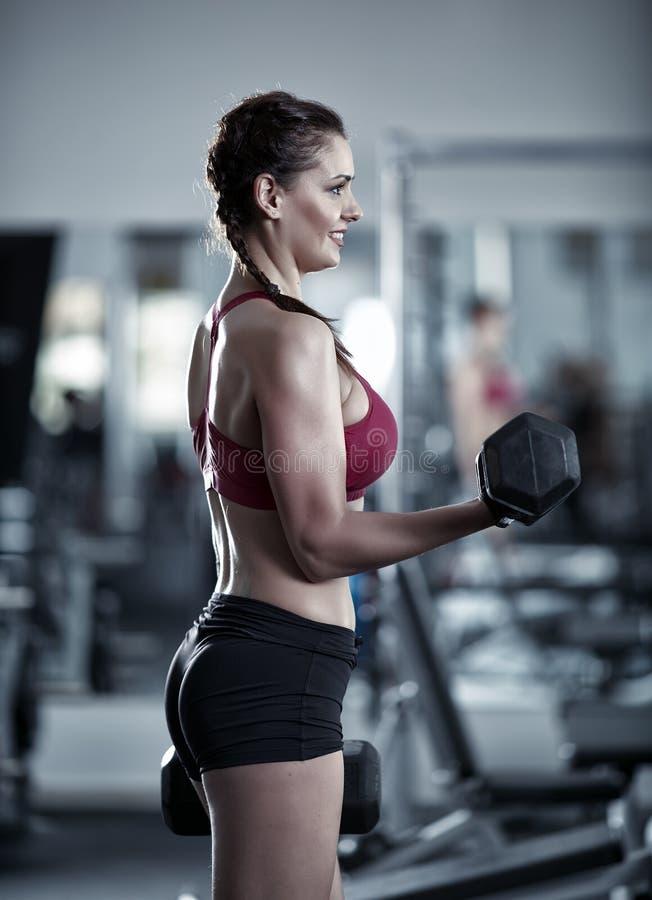 做二头肌锻炼的少妇 免版税库存照片