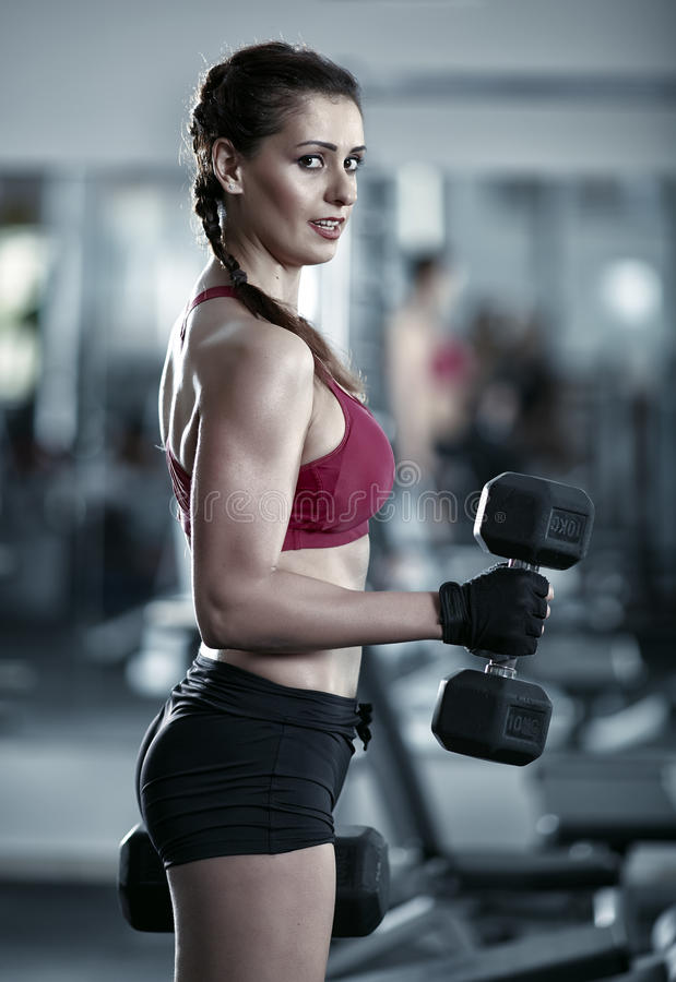 做二头肌锻炼的少妇 免版税库存图片