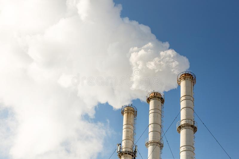 做云彩的烟斗反对蓝天背景 二氧化物空气污秽 危机生态学环境照片污染 免版税图库摄影