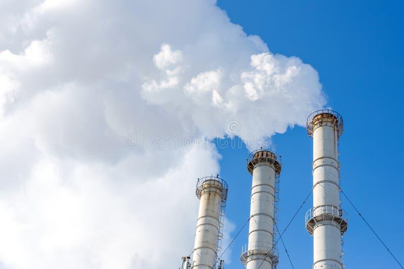 做云彩的烟斗反对蓝天背景 二氧化物空气污秽 危机生态学环境照片污染 免版税库存图片