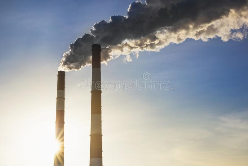 做云彩的烟斗反对蓝天背景 二氧化物空气污秽 危机生态学环境照片污染 nu的几天衰落  免版税库存图片