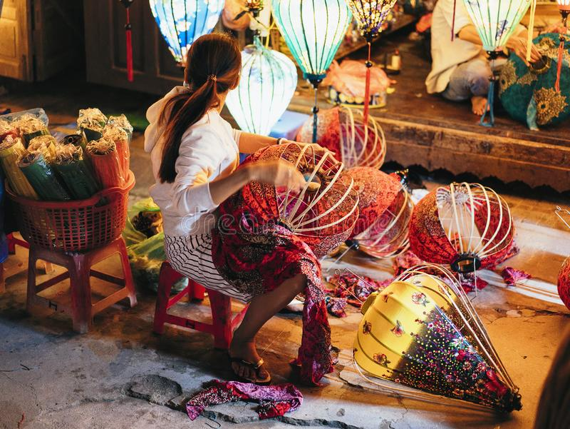 做五颜六色的传统会安市灯笼的越南妇女 库存照片
