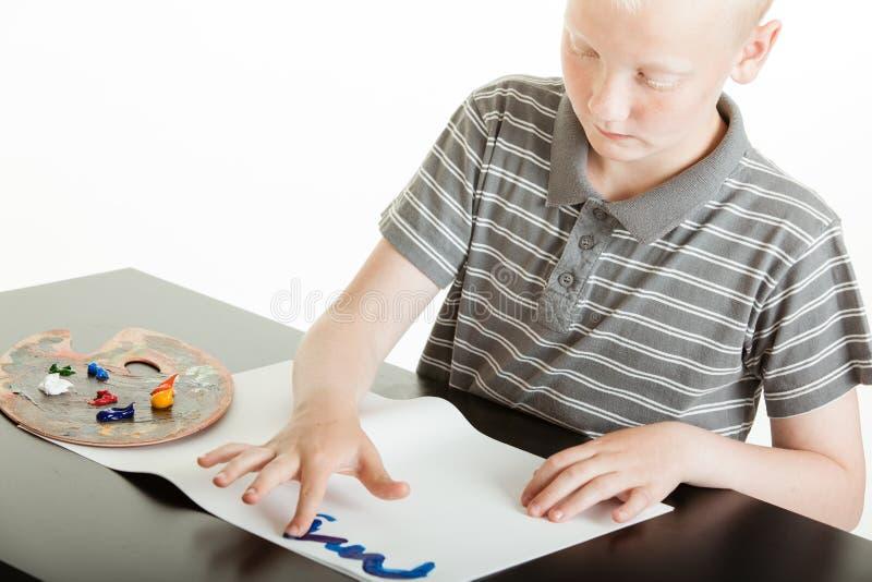 做五颜六色的手指画法的年轻男孩 库存照片