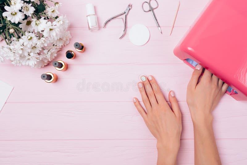 做五颜六色的胶凝体修指甲的平的布局过程 免版税库存照片