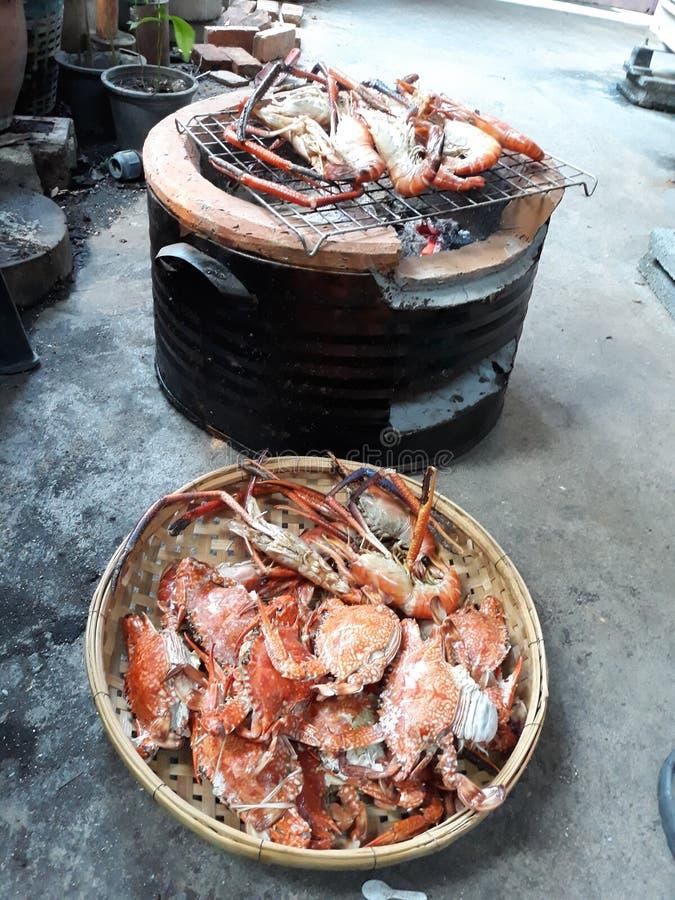 做亚洲样式烤食物,螃蟹和虾,在木炭火炉烧了,安置在一个热的火地板 免版税库存图片