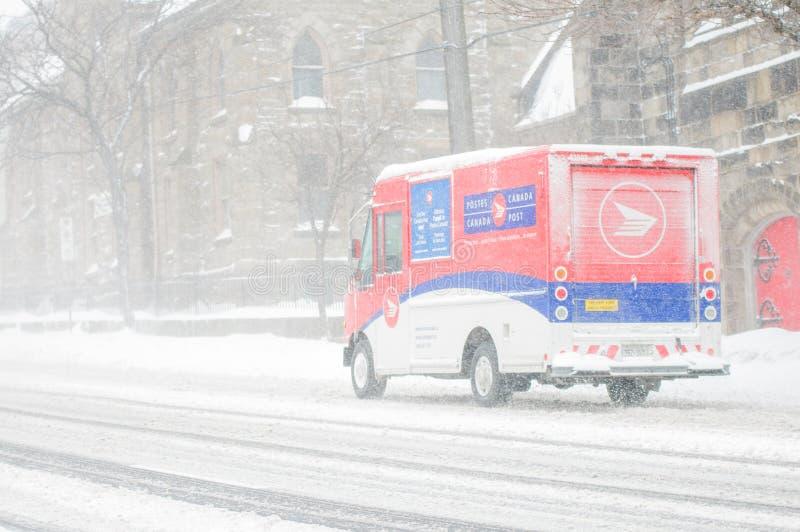 做交付的加拿大岗位送货卡车尝试在飞雪2013年2月期间 免版税图库摄影