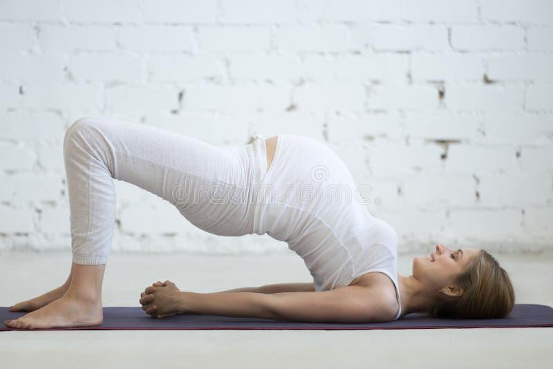 做产前瑜伽的怀孕的少妇 桥梁姿势 免版税库存图片