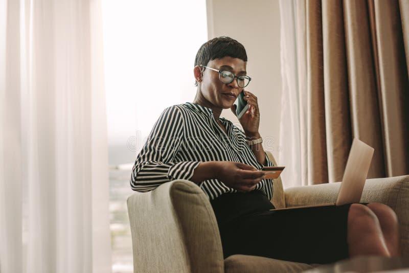 做从酒店房间的女实业家网上付款 库存照片